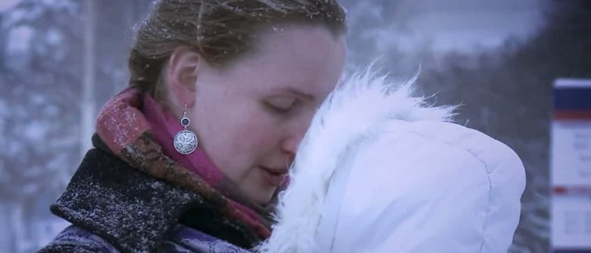A mother looks at her baby in the snow in the documentary Intro