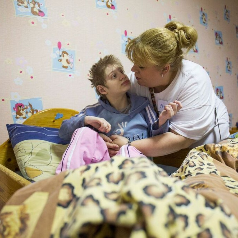 A nurse treats a boy with disabilities due to radiation exposure