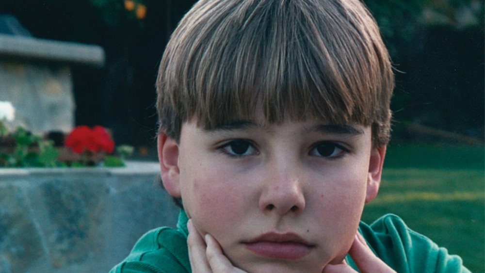 A young boy looks at the camera in the documentary An Open Secret